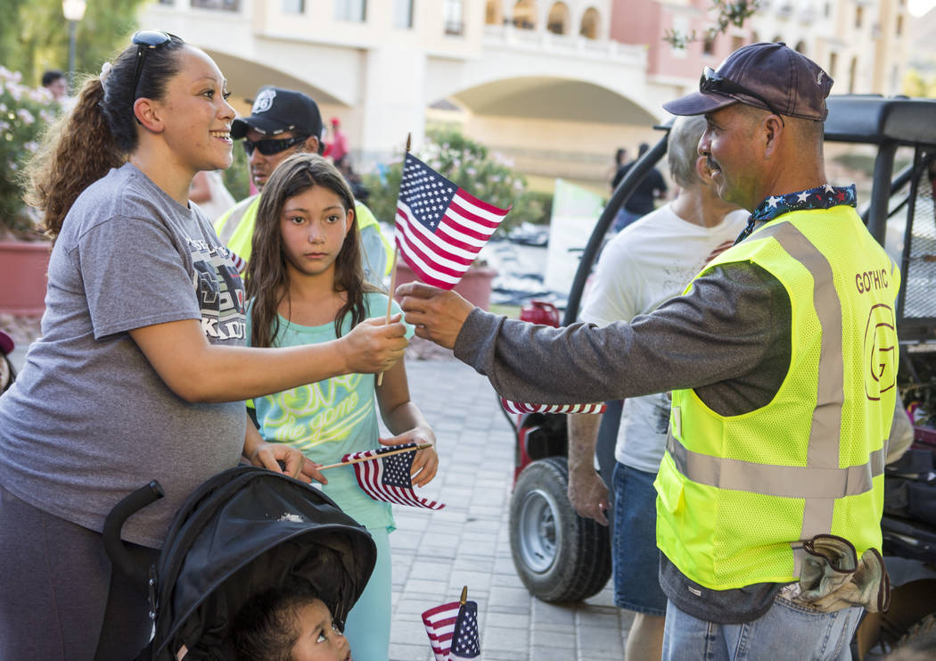 Latonya Brown takes a flag from Trino Nieves during Fourth of July weekend celebrations at Lake Las Vegas on Sunday, July 2, 2017.  Patrick Connolly Las Vegas Review-Journal @PConnPie