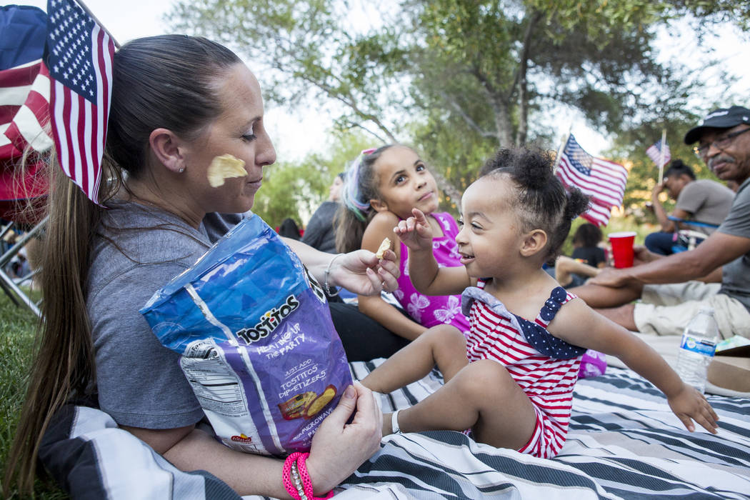 London McDonnell, 1, throws a chip past her mother Linzi McDonnell while Autumn McQuirter, 7, hangs out in the background during Fourth of July weekend celebrations at Lake Las Vegas on Sunday, Ju ...