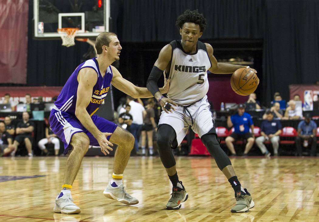 Sacramento Kings point guard De'Aaron Fox, right, is pressured by Los Angeles Lakers guard Alex Caruso during the NBA summer league at the Thomas & Mack Center in Las Vegas, Monday, July 10, 2 ...
