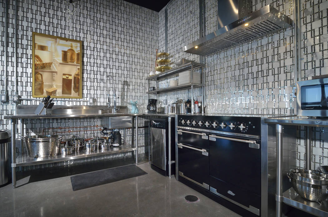 The kitchen is all about industrial style, but with a bit of glitz. It has no cabinets, utilizing open, commercial pieces instead. (Bill Hughes Real Estate Millions)
