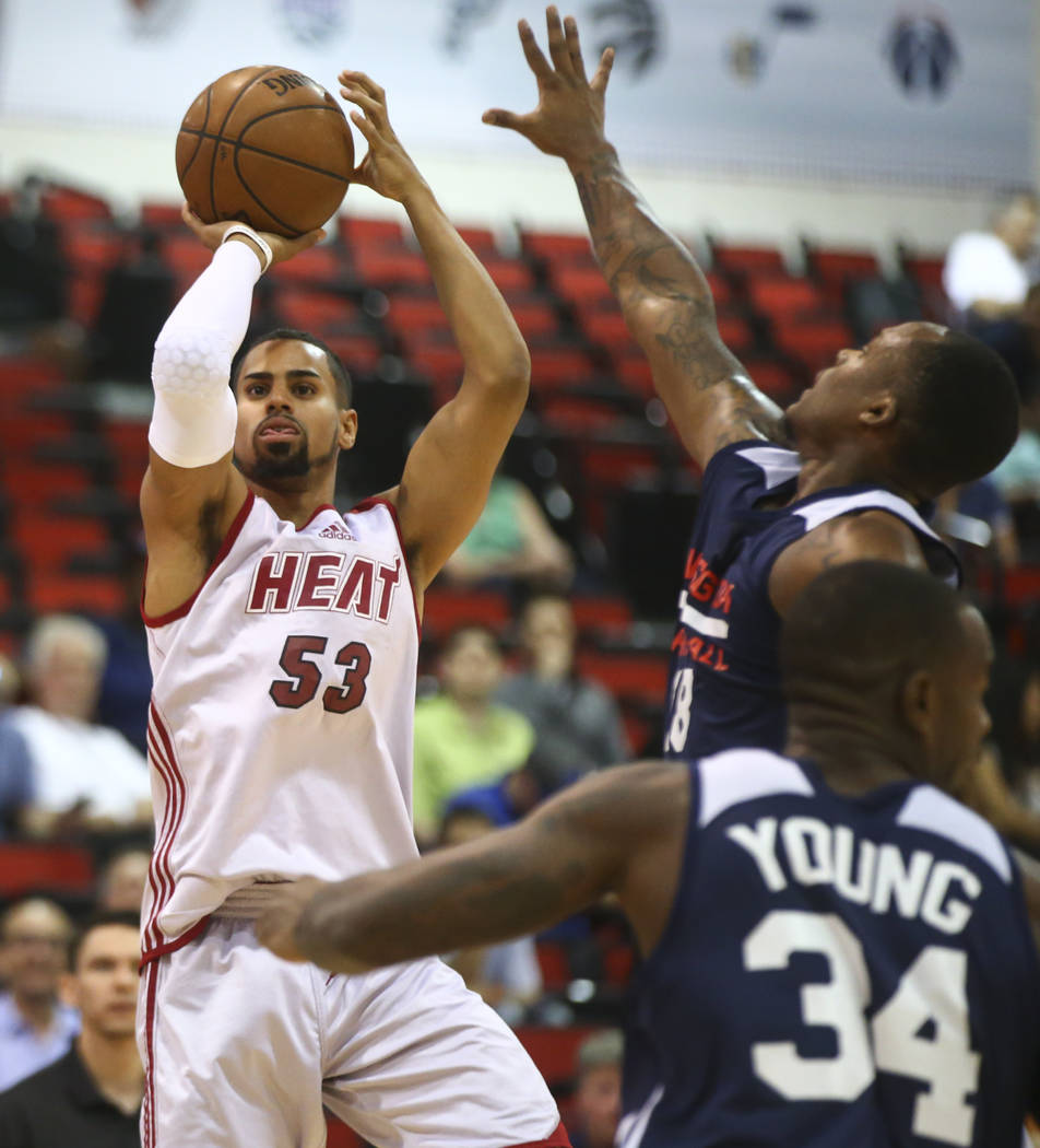 Miami Heat's Gian Clavell (53) shoots as Washington Wizards' Maalik Wayns (18) and Michael Young (34) defend during a basketball game at the NBA Summer League at the Cox Pavilion in Las Vegas on W ...