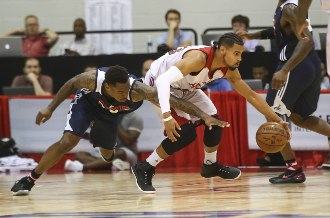Miami Heat's Gian Clavell (53) drives past Washington Wizards' Sheldon McClellan (9) during a basketball game at the NBA Summer League at the Cox Pavilion in Las Vegas on Wednesday, July 12, 2017. ...