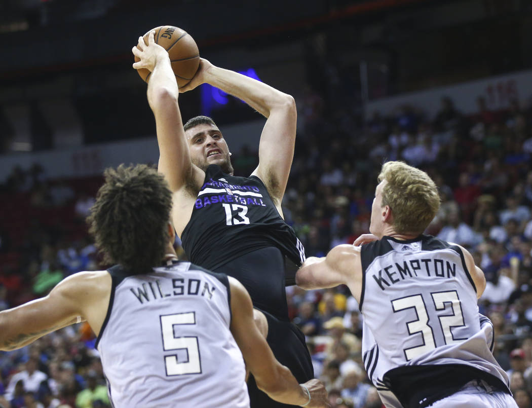 Sacramento Kings' Georgios Papagiannis (13) goes to the basket between Milwaukee Bucks' D.J. Wilson (5) and Tim Kempton (32) during a basketball game at the NBA Summer League at the Thomas & M ...