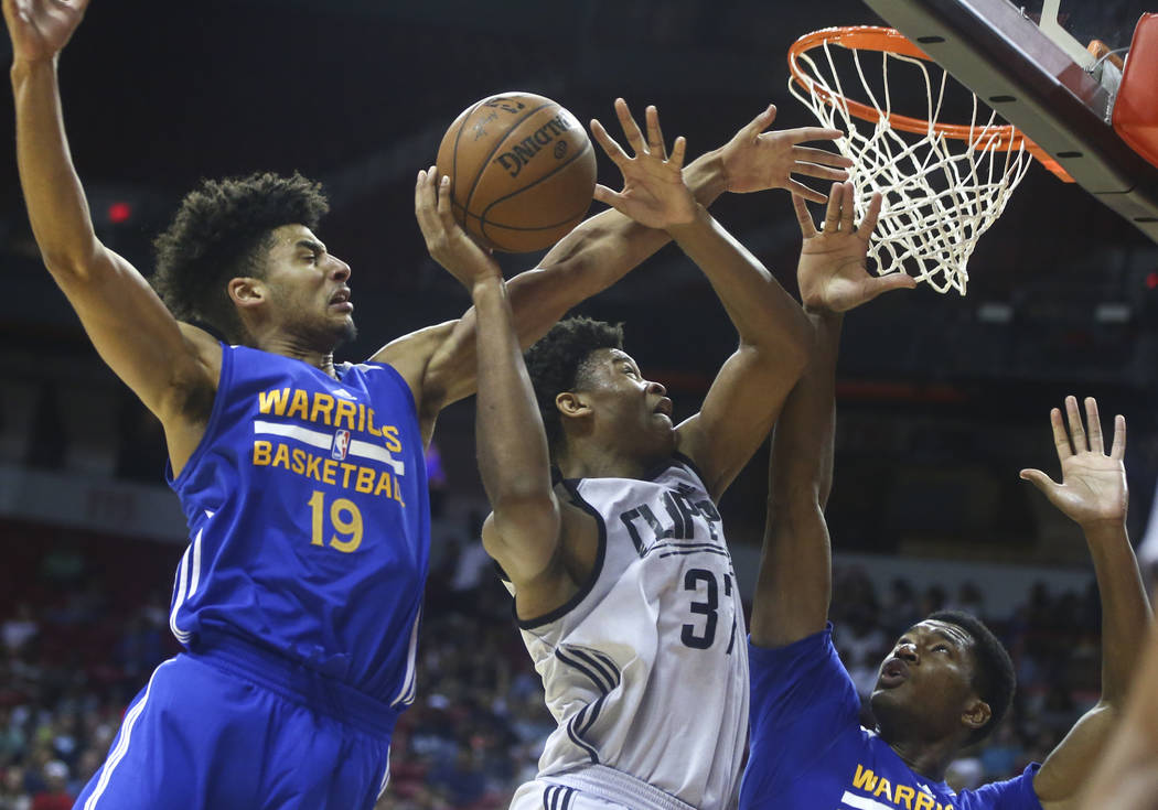 Golden State Warriors' Tai Webster (19) and Damian Jones, lower right, defend as Los Angeles Clippers' Isaiah Hicks (37) goes to the basket during a basketball game at the NBA Summer League at the ...