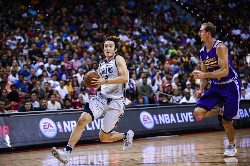 Dallas Mavericks forward Ding Yanyuhang, left, heads toward the net against Los Angeles Lakers forward Brandon Ingram during the NBA Summer League semifinal game at Thomas and Mack Center on Sunda ...