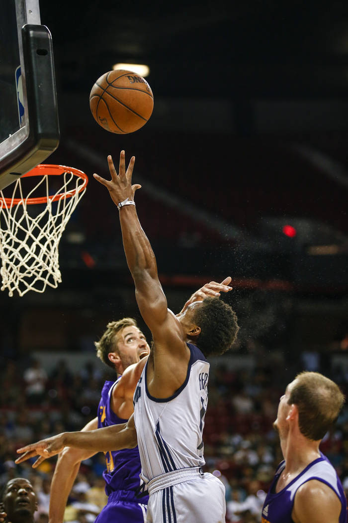 Dallas Mavericks guard Yogi Ferrell, center, and Los Angeles Lakers forward Travis Wear, left, battle for a rebound during the NBA Summer League semifinal game at Thomas and Mack Center on Sunday, ...