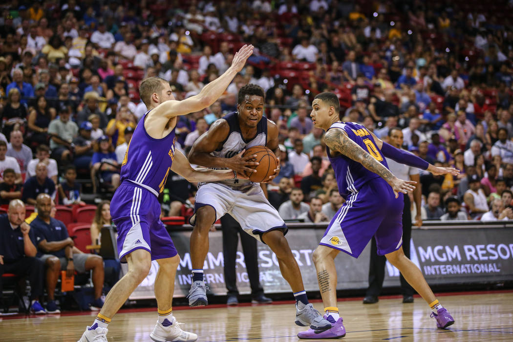 Dallas Mavericks guard Yogi Ferrell, center, defends the ball against Los Angeles Lakers forward Travis Wear, left,  and Los Angeles Lakers forward Kyle Kuzma, right, during the NBA Summer League  ...