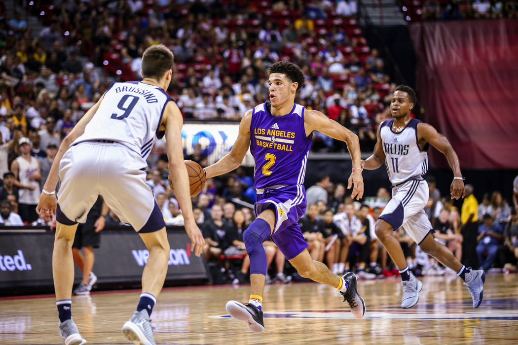 Los Angeles Lakers guard Lonzo Ball (2) tries to drive past Dallas Mavericks guard Nicolas Brussino (9) as guard Yogi Ferrell (11) runs during the NBA Summer League semifinal game at Thomas and Ma ...