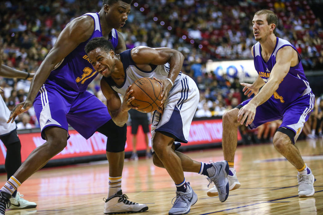 Dallas Mavericks guard Yogi Ferrell, center, keeps a ball away from Los Angeles Lakers center Thomas Bryant, left, and forward Brandon Ingram during the NBA Summer League semifinal game at Thomas  ...