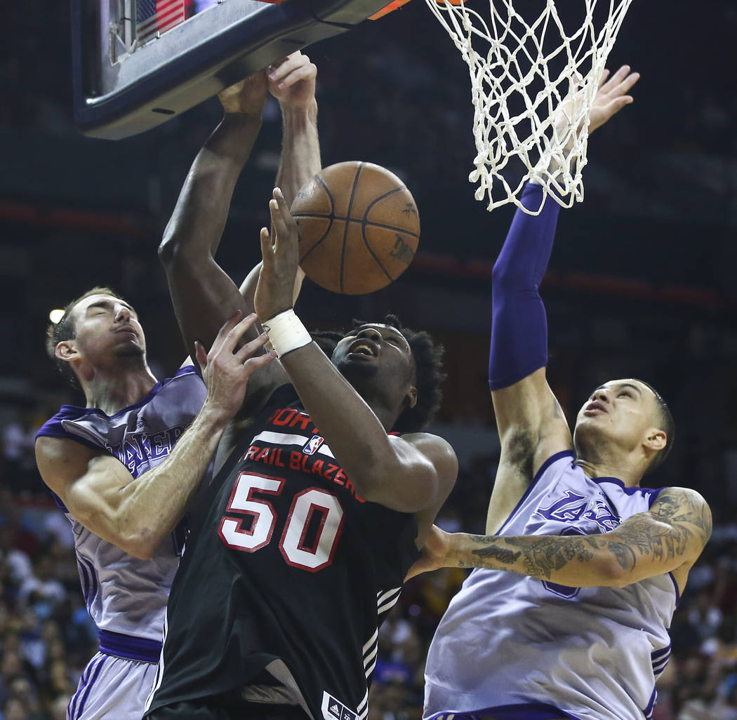 Los Angeles Lakers' Alex Caruso (4) and Los Angeles Lakers' Kyle Kuzma (0) defend as Portland Trail Blazers' Caleb Swanigan (50) goes to the basket during the NBA Summer League championship game a ...
