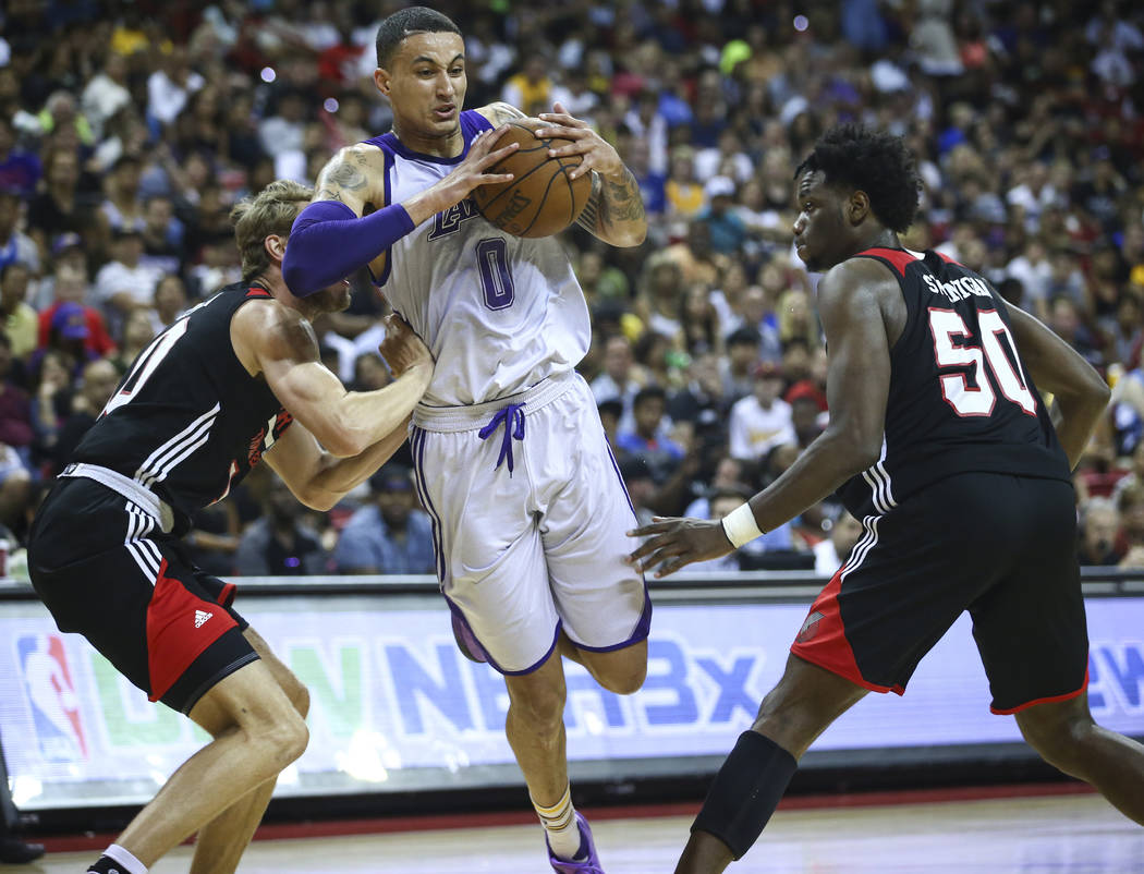 Portland Trail Blazers' Jake Layman (10) and Caleb Swanigan defend as Los Angeles Lakers' Kyle Kuzma drives to the basket during the NBA Summer League championship game at the Thomas & Mack Ce ...