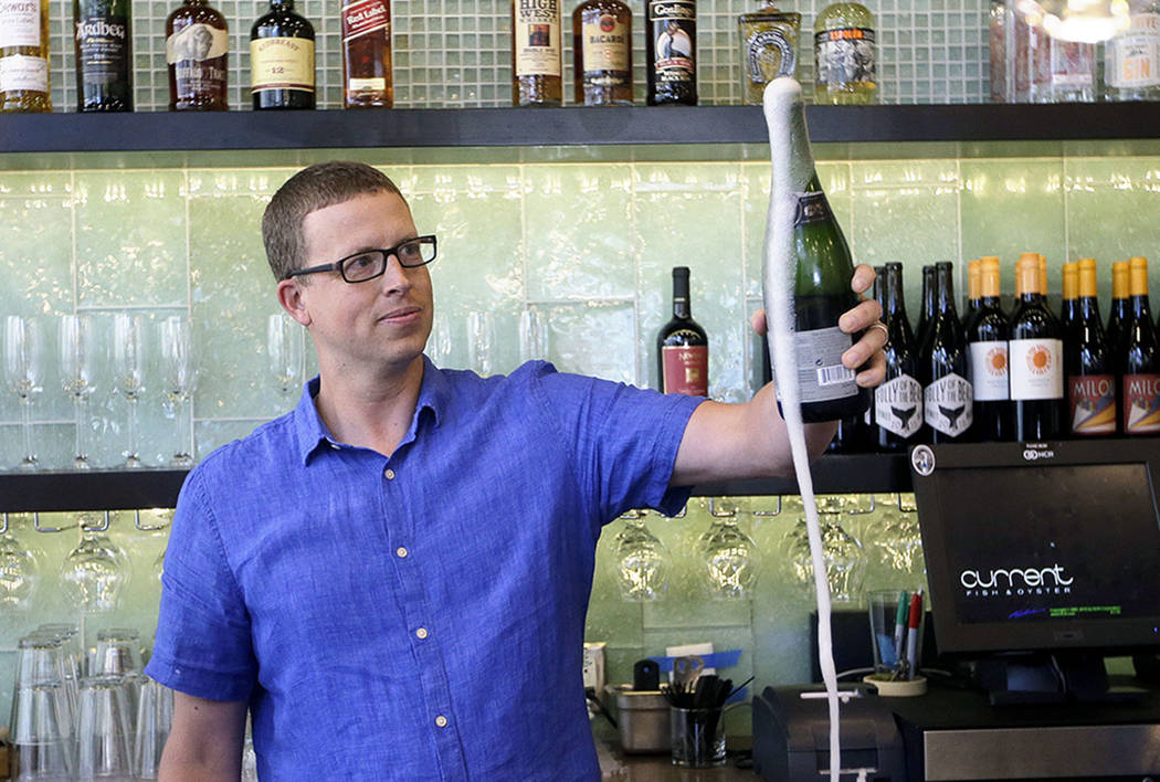"Andrew Cliburn opens a bottle of champagne after a partition known as the ""Zion Curtain"" that prevents customers from seeing their alcoholic drinks being mixed and poured, was taken down at Curren ..."