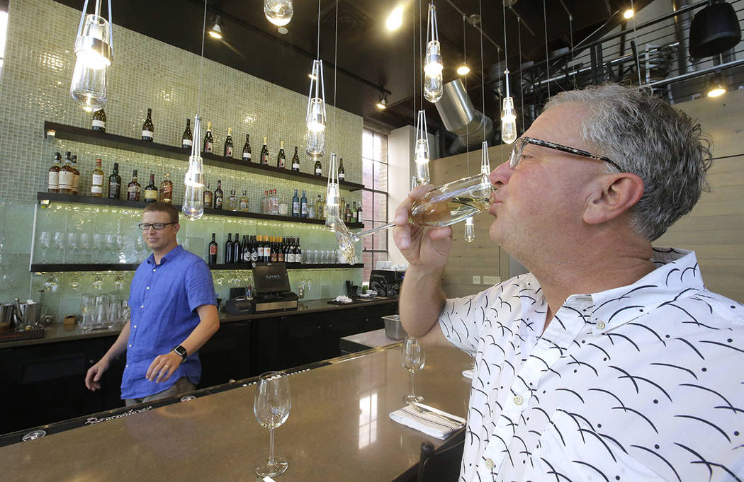 "Andrew Cliburn, left, looks on after pouring a glass of champagne to Joel LaSalle, Current Fish and Oyster owner, after a partition known as the ""Zion Curtain"" that prevents customers from seeing  ..."