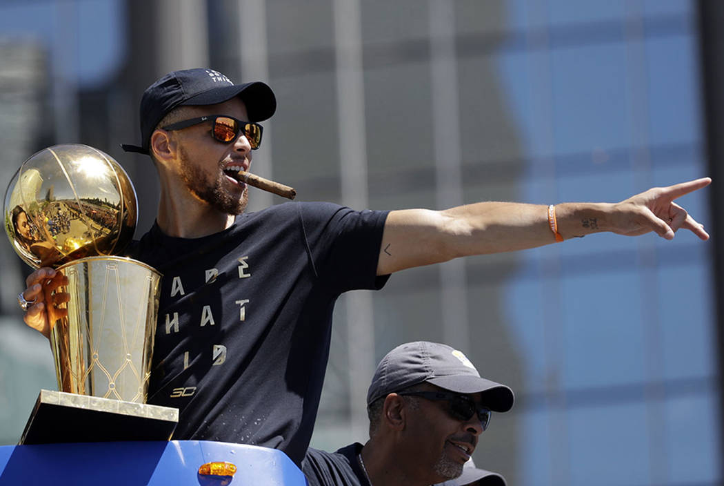 Golden State Warriors Stephen Curry Gestures While Holding The Larry OBrien Trophy During