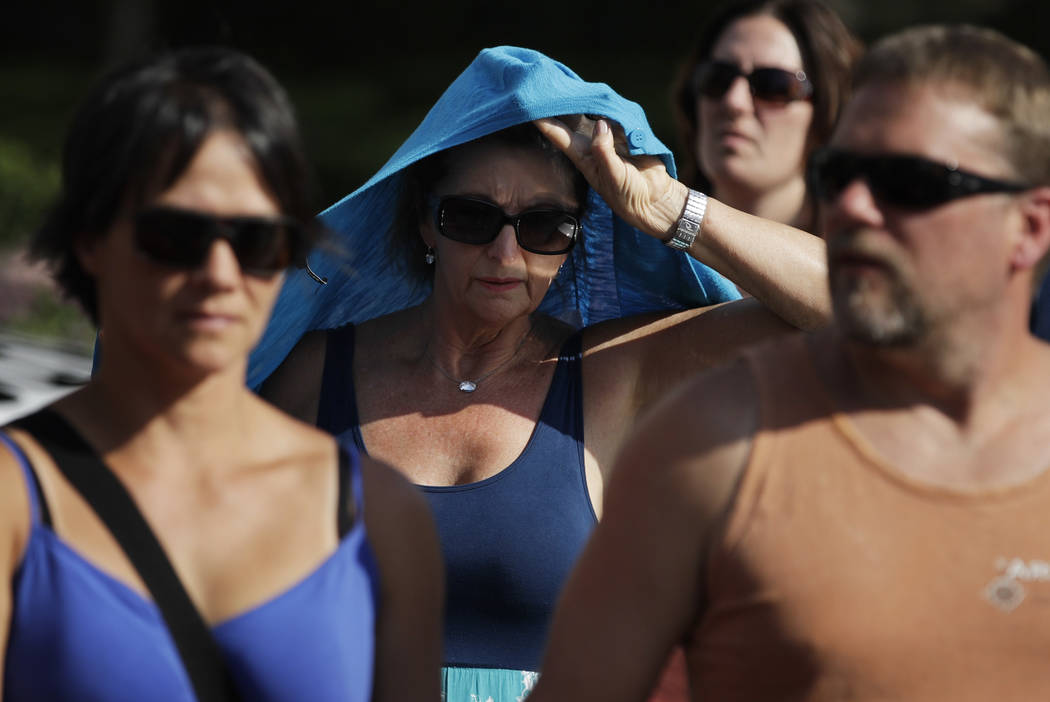 A woman shields herself from the sun while walking along the Las Vegas Strip, Tuesday, June 20, 2017, in Las Vegas. (John Locher/AP)