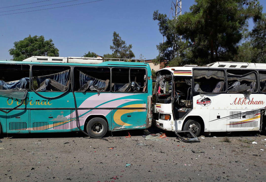 This photo released by the Syrian official news agency SANA, shows several damaged buses along the road to the airport in southeast Damascus, Syria, Sunday, July 2, 2017. (SANA via AP)