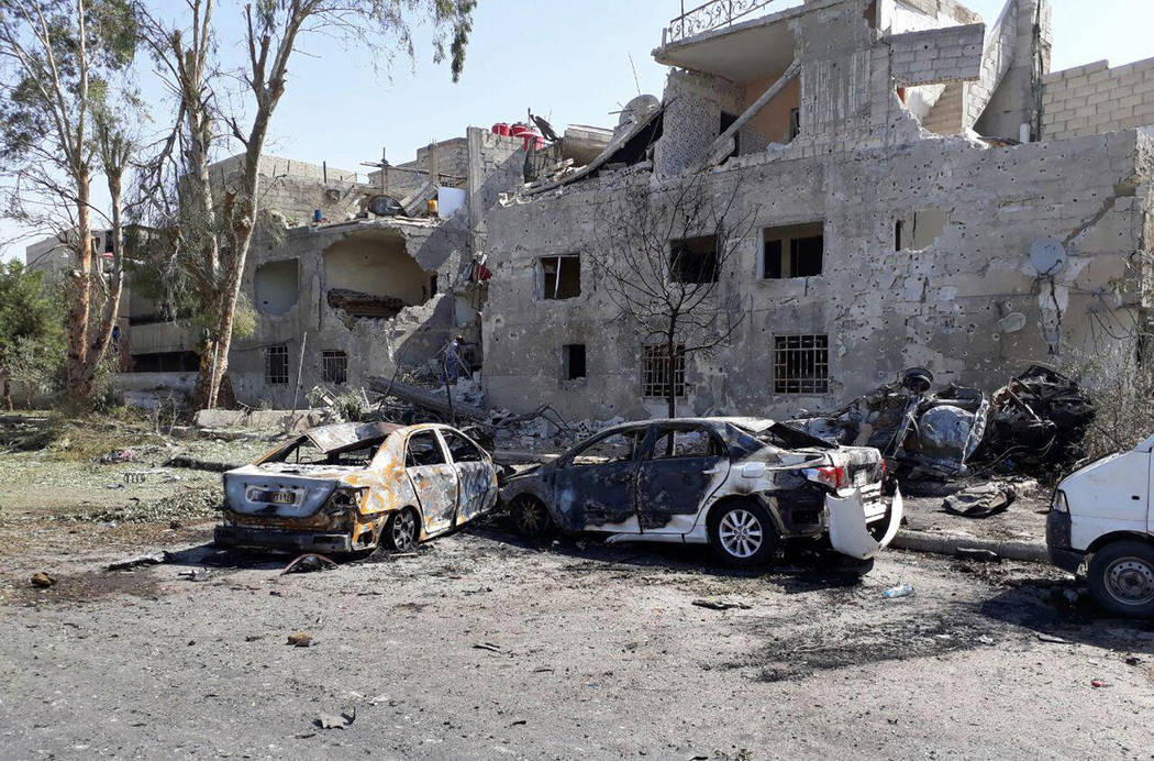 In this photo released by the Syrian official news agency SANA, shows several damaged cars along the road to the airport in southeast Damascus, Syria, Sunday, July 2, 2017. Syrian state TV said Su ...