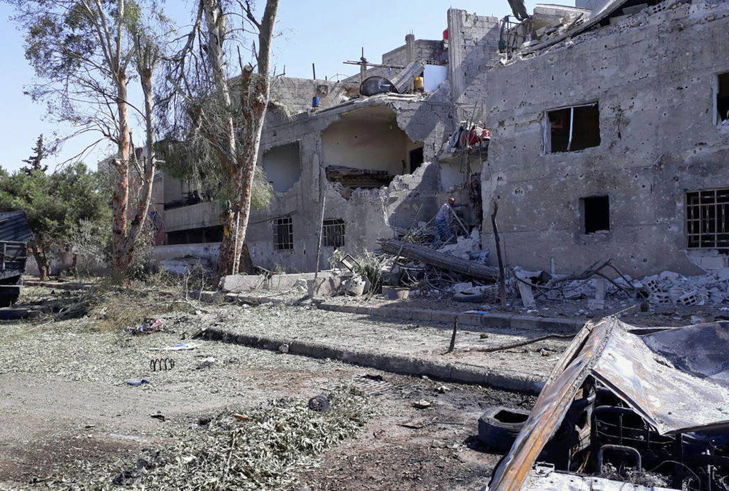 This photo released by the Syrian official news agency SANA, shows damaged buildings at the scene of an explosion along the road to the airport in southeast Damascus, Syria, Sunday, July 2, 2017.  ...