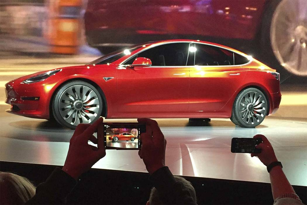 In this March 31, 2016, file photo, Tesla Motors unveils the new lower-priced Model 3 sedan at the Tesla Motors design studio in Hawthorne, California. The Model 3 car will go on sale Friday. (Jus ...