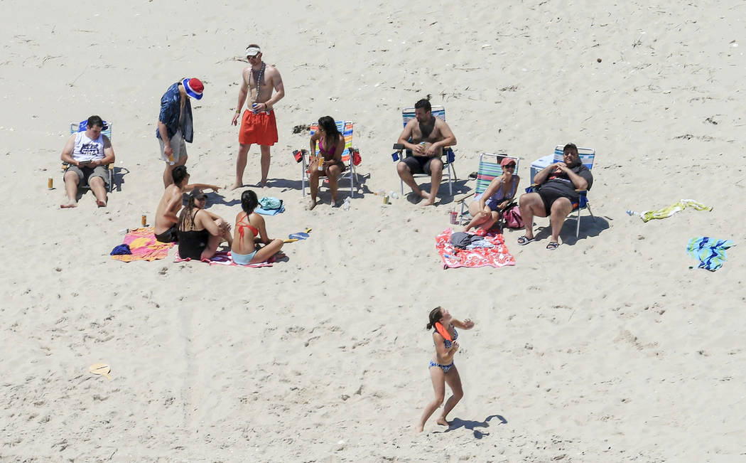 In this Sunday, July 2, 2017, photo, New Jersey Gov. Chris Christie, right, uses the beach with his family and friends at the governor's summer house at Island Beach State Park in New Jersey. Chri ...