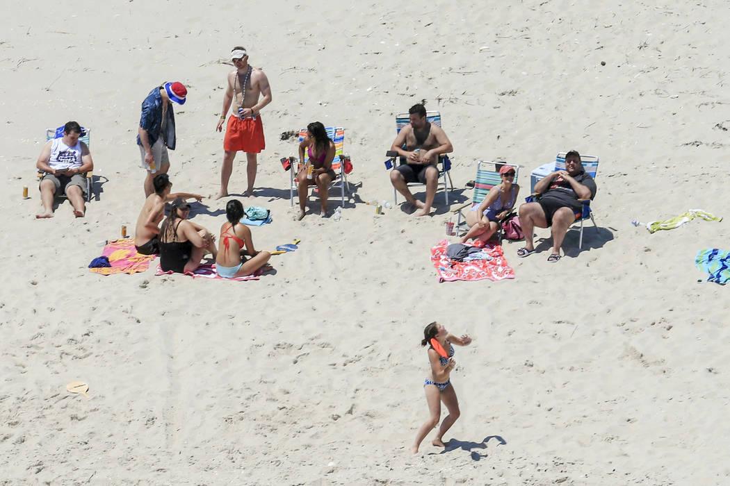 New Jersey Gov. Chris Christie, right, uses the beach Sunday, July 2, 2017, with his family and friends at the governor's summer house at Island Beach State Park in New Jersey. Christie is defendi ...