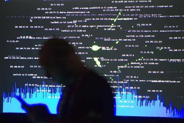 Black Hat tech associate Gordon Cooper looks at his phone as he works in the network operating center during the Black Hat convention at Mandalay Bay convention center in Las Vegas on Thursday, Au ...
