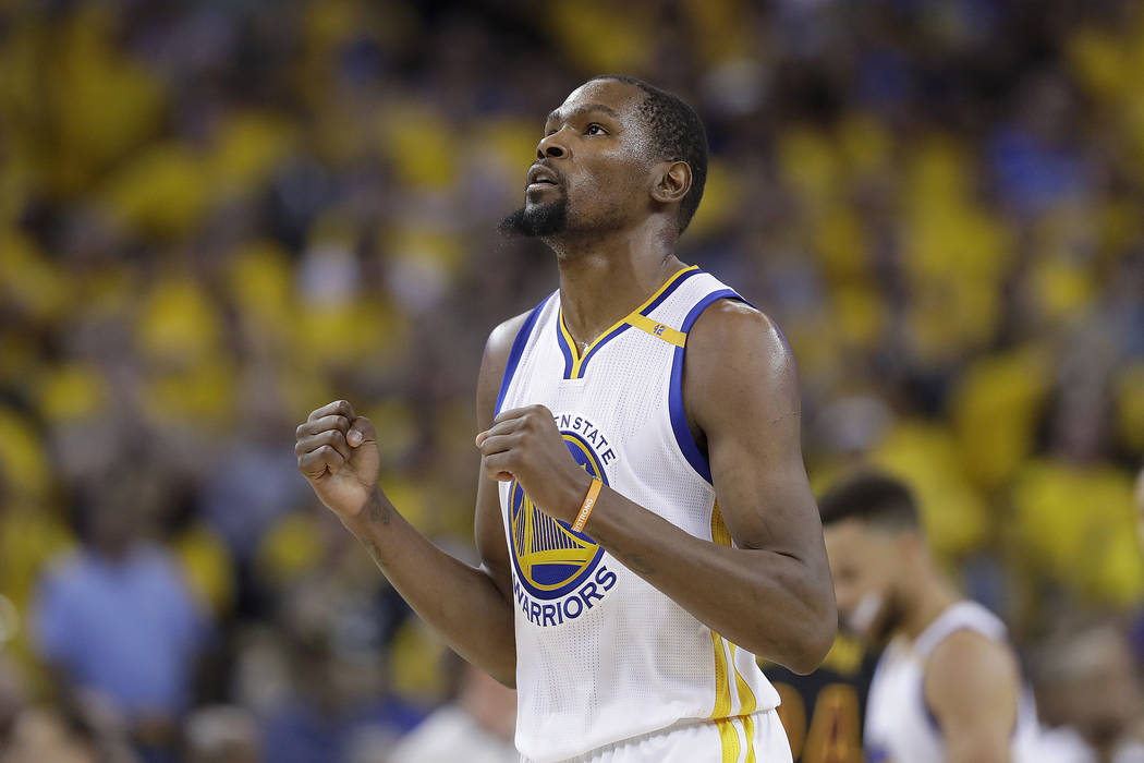 In this June 12, 2017 file photo, Golden State Warriors forward Kevin Durant reacts after scoring against the Cleveland Cavaliers during the second half of Game 5 of basketball's NBA Finals in Oak ...