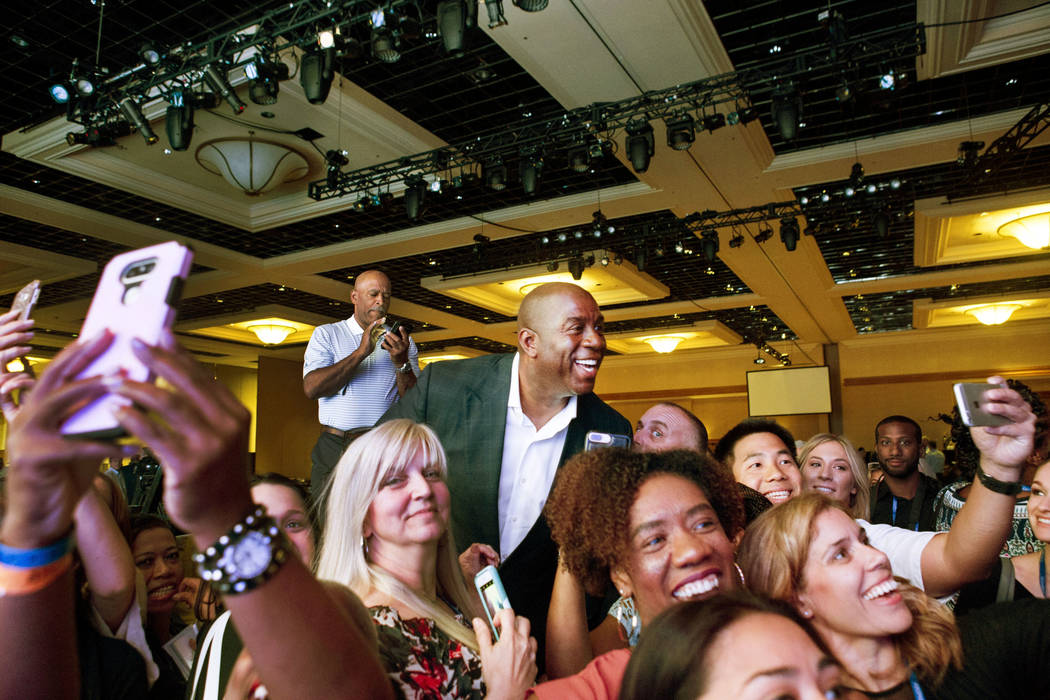 """Businessman and former basketball star Earvin """"Magic"""" Johnson takes pictures with attendees of the Professional Beauty Association Business Forum during Cosmoprof North America a ..."""