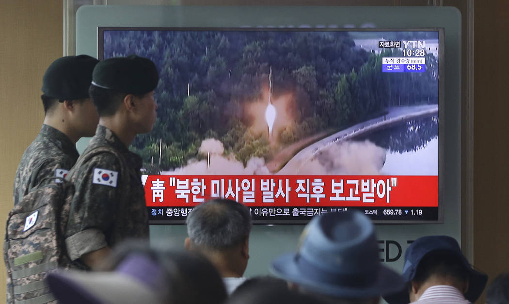 Army soldiers walk by a TV news program showing a file image of a missile being test-launched by North Korea at the Seoul Railway Station in Seoul, South Korea, Tuesday, July 4, 2017. North Korea  ...