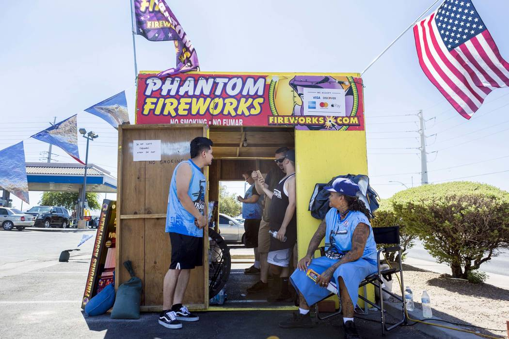 The Las Vegas Wranglers, a not-for-profit slow-pitch softball team, wait for costumers to sell fireworks at a Phantom Fireworks Stand on Warm Springs Road and Las Vegas Boulevard in Las Vegas, Mon ...