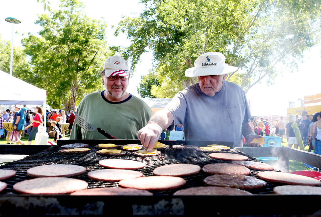 Bryon Schroeder, left, and Keith Eland, cook hamburgers during the 69th Annual Boulder City Damboree Celebration in Boulder City, Tuesday, July, 4, 2017. (Elizabeth Brumley/Las Vegas Review-Journal)
