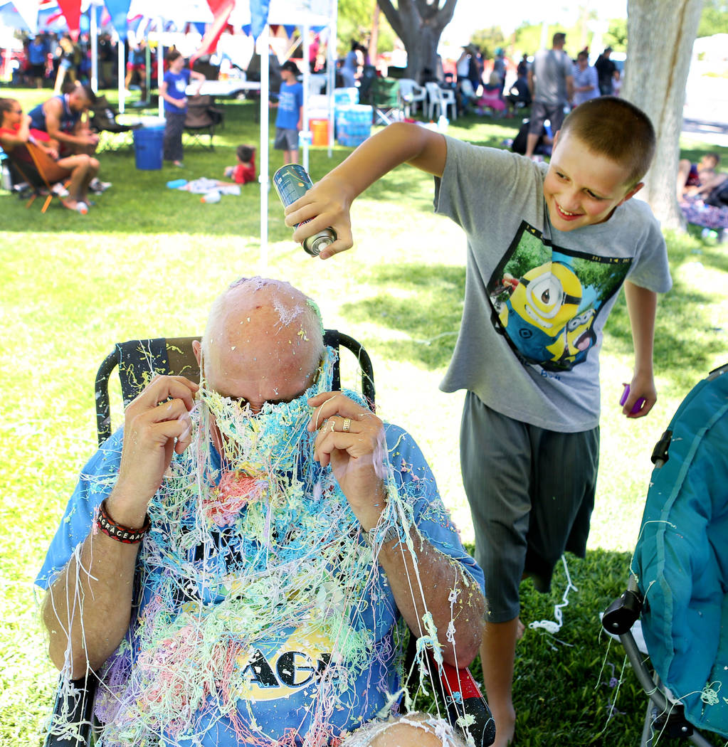 Terry Warner, left, gets sprayed with silly string by Aaron Hirsbrunner, 11, during the 69th Annual Boulder City Damboree Celebration in Boulder City, Tuesday, July, 4, 2017. (Elizabeth Brumley/La ...