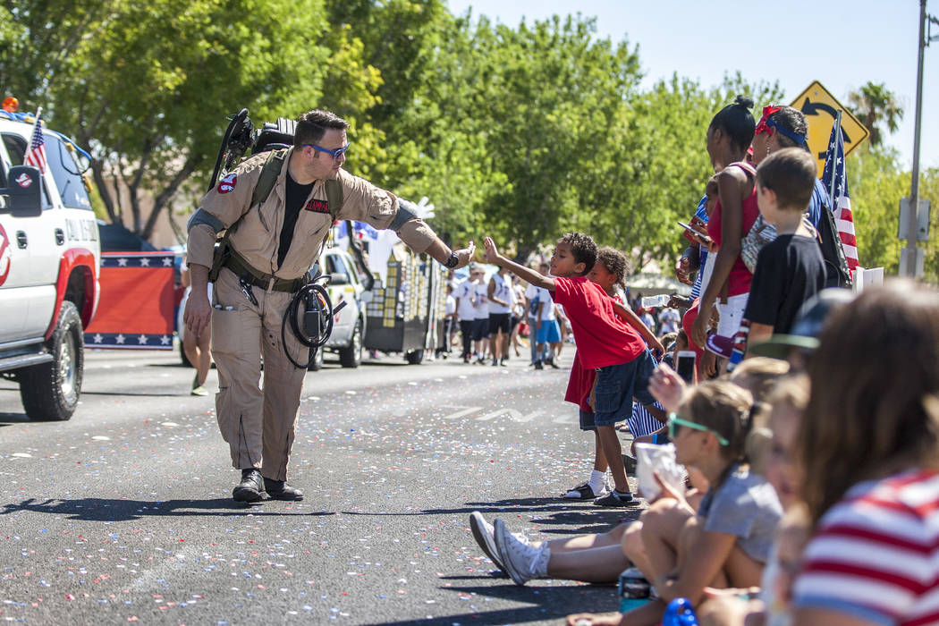 A ghostbuster high-fives a young paradegoer during the Summerlin Council Patriotic Parade in Summerlin on Tuesday, July 4, 2017.  (Patrick Connolly/Las Vegas Review-Journal) @PConnPie