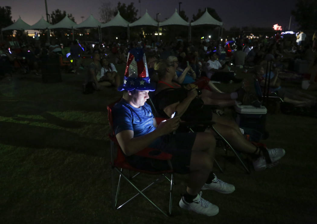 A man checks his phone during the fireworks show at the City of Henderson's Fourth of July celebration at Heritage Park in Henderson, Tuesday, July 4, 2017. (Gabriella Angotti-Jones/Las Vegas Revi ...