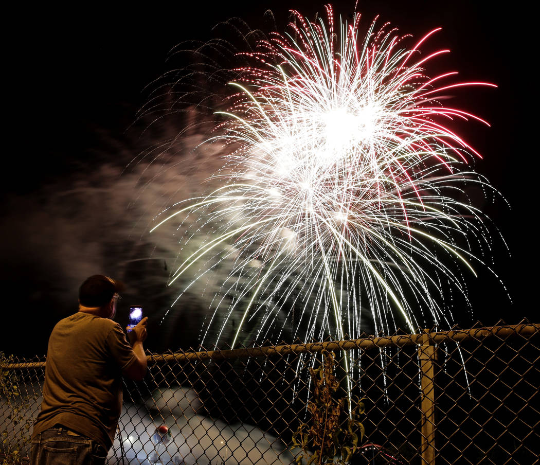 A man watches a fireworks display for Independence Day at Worlds of Fun amusement park Monday, July 3, 2017, in Kansas City, Mo. (Charlie Riedel/AP)