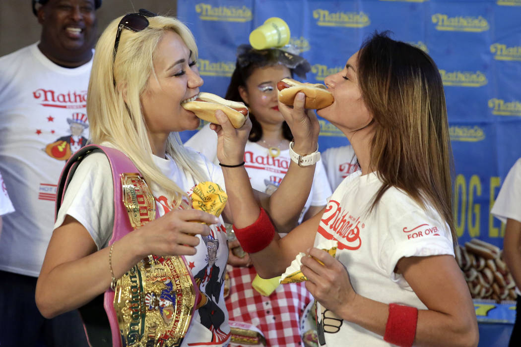 Current women's champion Miki Sudo, left, of Las Vegas, and challenger Michelle Lesco, of Tuscon, Ariz., feed each other a hot dog Monday, July 3, 2017, during the weigh-in for the 2017 Nathan's H ...