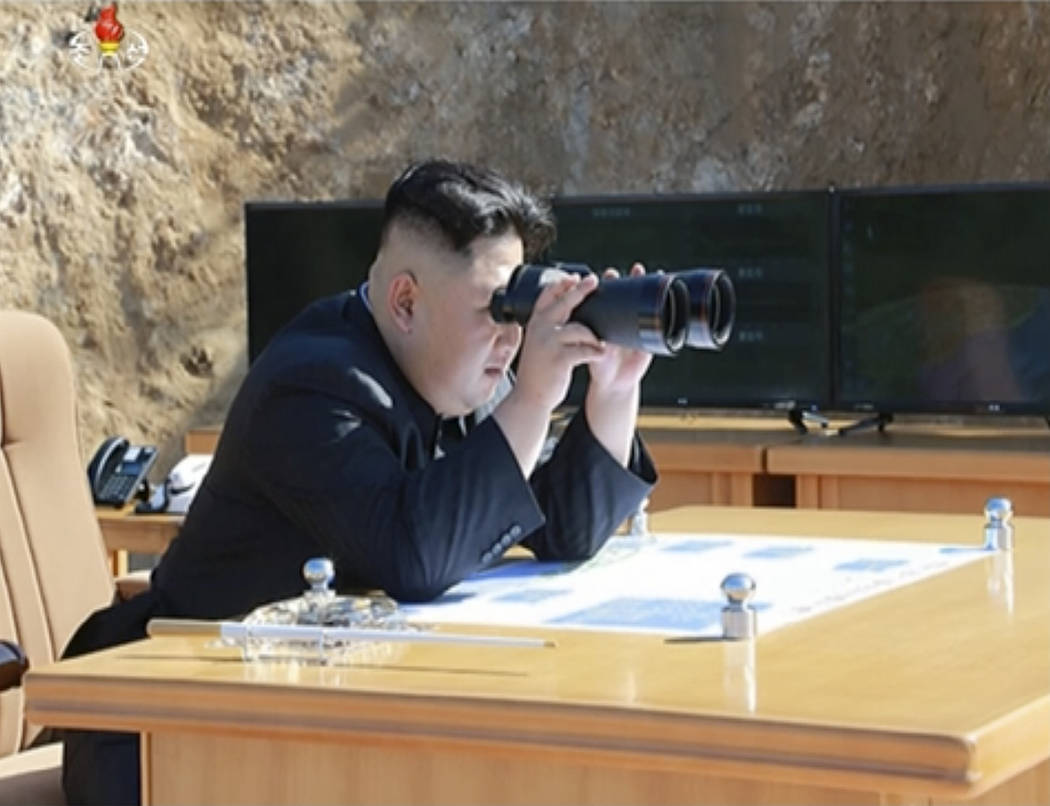 This image made from video of a news bulletin aired by North Korea's KRT on Tuesday, July 4, 2017, shows what was said to be North Korea leader Kim Jung Un, center, using binoculars to watch the l ...