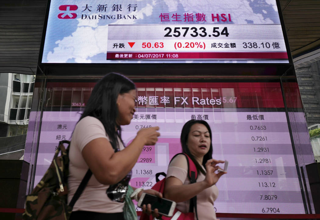 People walk past an electronic board showing the Hong Kong Stock Exchange index, Tuesday, July 4, 2017, in Hong Kong, China. Australian shares jumped Tuesday as investors awaited an interest rate  ...