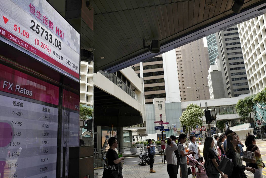 People stand next to an electronic board showing the Hong Kong Stock Exchange index, Tuesday, July 4, 2017, in Hong Kong, China. Australian shares jumped Tuesday as investors awaited an interest r ...