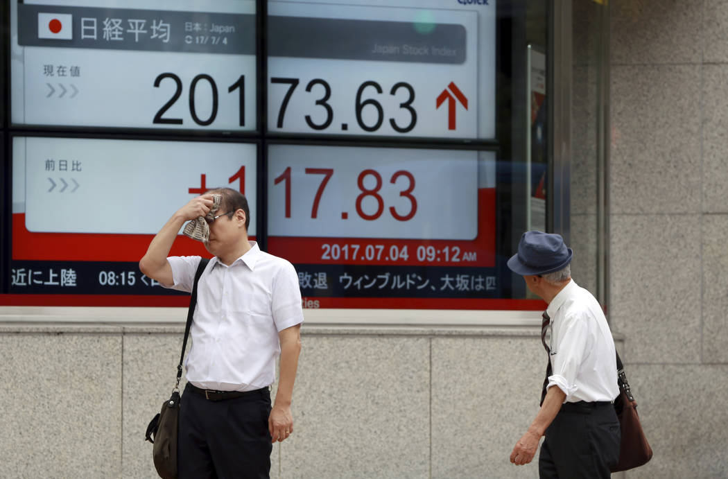 Men stand near an electronic stock board showing Japan's Nikkei 225 index at a securities firm in Tokyo Tuesday, July 4, 2017. Australian shares jumped Tuesday as investors awaited the central ban ...