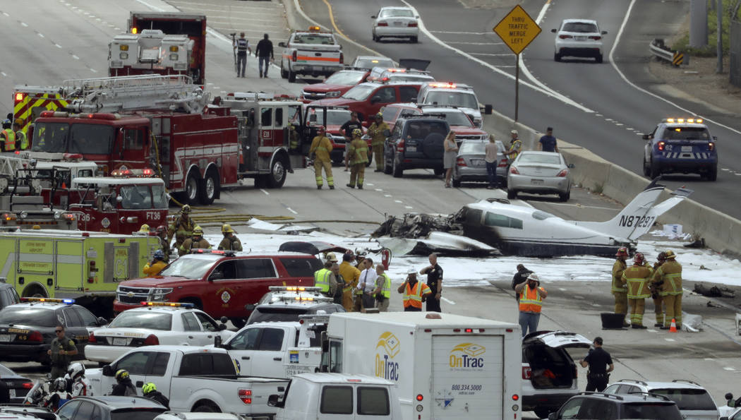 Emergency responders gather round the crash of a Cessna 310 aircraft on Interstate 405, just short of a runway at John Wayne Airport in Costa Mesa, Calif., Friday, June 30, 2017. Two people were i ...