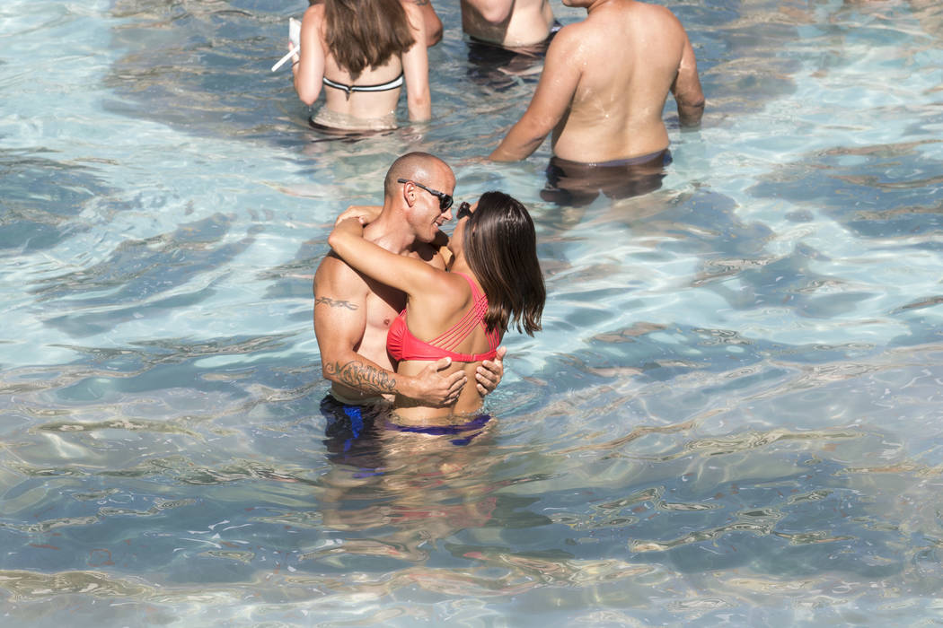 A couple shares a moment while swimming at the Garden of the Gods Pool Oasis at Caesars Palace in Las Vegas on Tuesday, July 4, 2017.  Richard Brian Las Vegas Review-Journal @vegasphotograph