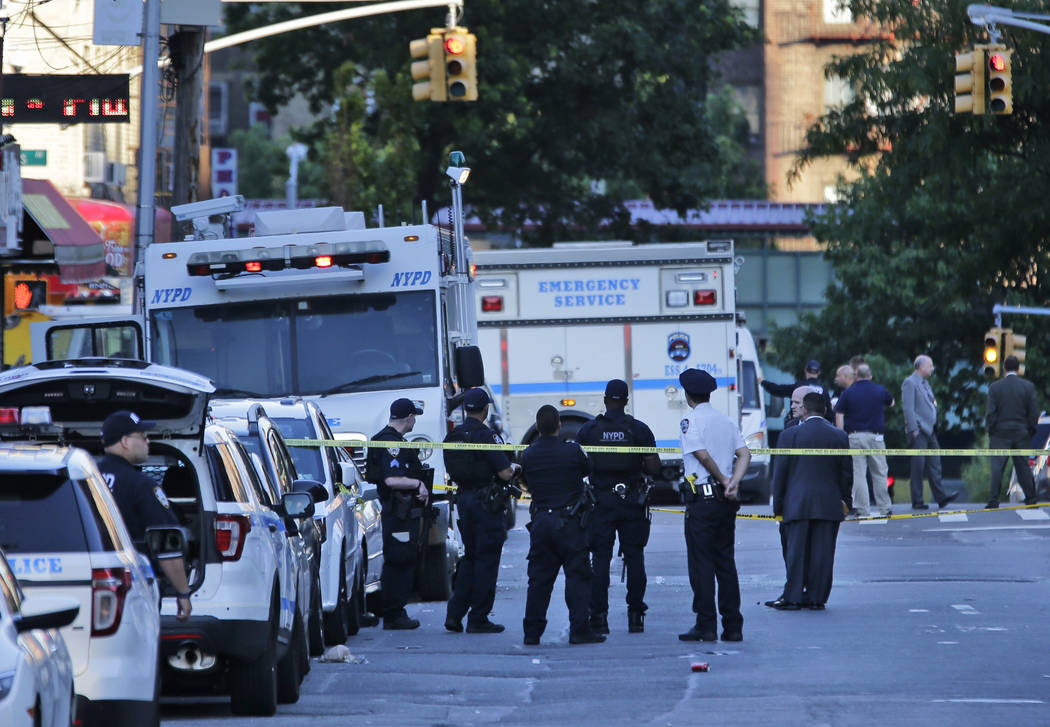 Emergency personnel stand near the scene where a police officer was fatally shot while sitting in a marked vehicle in the Bronx section of New York, Wednesday, July 5, 2017. Police said Officer Mi ...