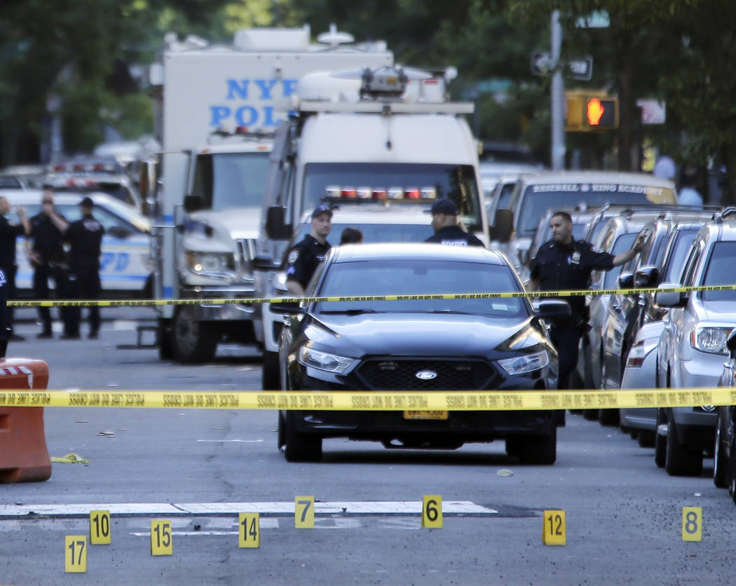 Numbers mark a crime scene near the site where a police officer was fatally shot in the Bronx section of New York, Wednesday, July 5, 2017. Police said other officers shot and killed the suspect a ...