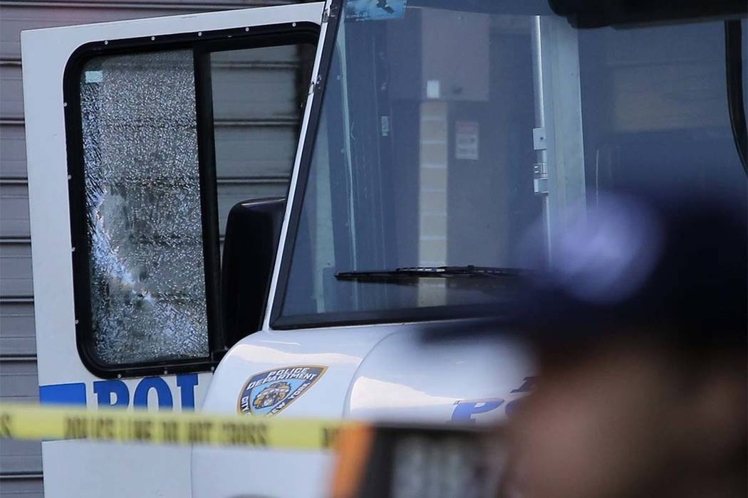 An NYPD vehicle with a cracked window sits on the scene where a police officer was fatally shot in the Bronx section of New York, Wednesday, July 5, 2017. Police said other officers shot and kille ...