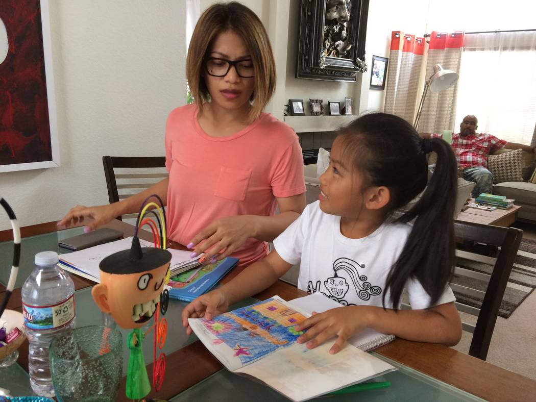 Hope Mathis, 7,  reads from her book May 30, 2017, as her mother, Reah, looks on.  The books introduces the characters who inhabit the fictional Esperer Island. The illustrations in the book were  ...
