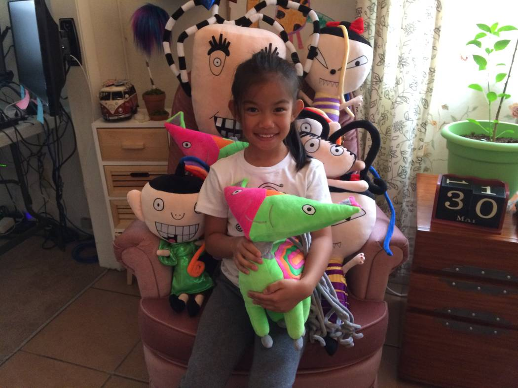 Hope Mathis, 7,  poses with some of the plush toys of her characters May 30, 2017 in the family's Desert Shores home.  A book  introduces the characters on the fictional Esperer Island. The illust ...