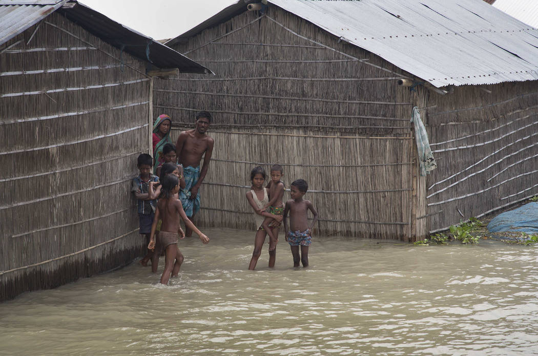 Indian villagers stand outside their houses partially submerged in flood waters in Burgaon, 50 miles east of Gauhati, Assam state, India, Wednesday, July 5, 2017. Heavy rains since the start of In ...