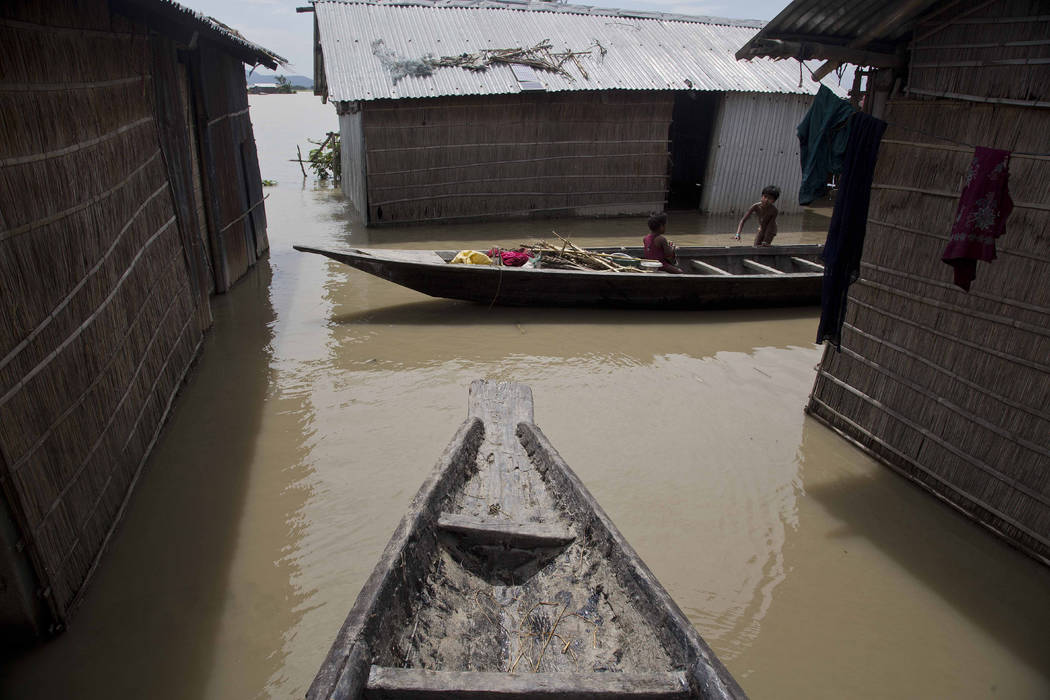 An Indian child sits in a boat as another stands near their house partially submerged in flood waters in Burgaon, 50 miles east of Gauhati, Assam state, India, Wednesday, July 5, 2017. Heavy rains ...