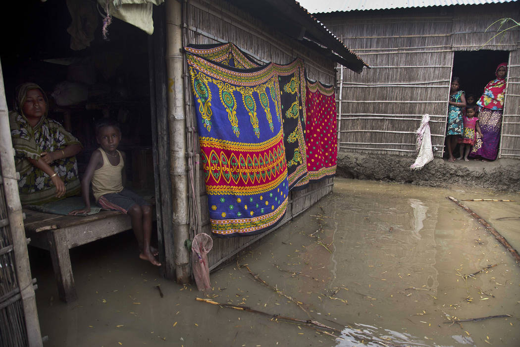 Indian villagers look out from inside their houses partially submerged in flood waters in Burgaon, 50 miles east of Gauhati, Assam state, India, Wednesday, July 5, 2017. Heavy rains since the star ...
